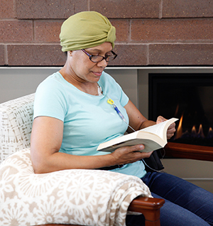 Woman sitting at home reading, with chemo infusion port in chest.