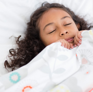 Child sleeping with covers up around her face as if scared.