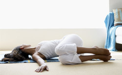 Woman doing back flexibility exercise on a mat on the floor