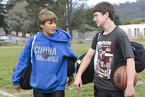 Two teen boys with sports gear talking outside.